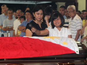 Atty. Leni Robredo and daughters Aika, Patricia and Jillian sprinkle Holy Water on the flag-draped casket of Department of Interior and Local Government Secretary Jesse Robredo during the Holy Mass at the Archbishop's Palace in Naga City Tuesday night (Aug. 21, 2012). President Benigno S. Aquino III has signed Proclamation No. 460 declaring National Days of Mourning starting Aug. 21 to mark the death of Robredo until his interment. (Photo by: Ryan Lim/ Malacañang Photo Bureau/PNA)