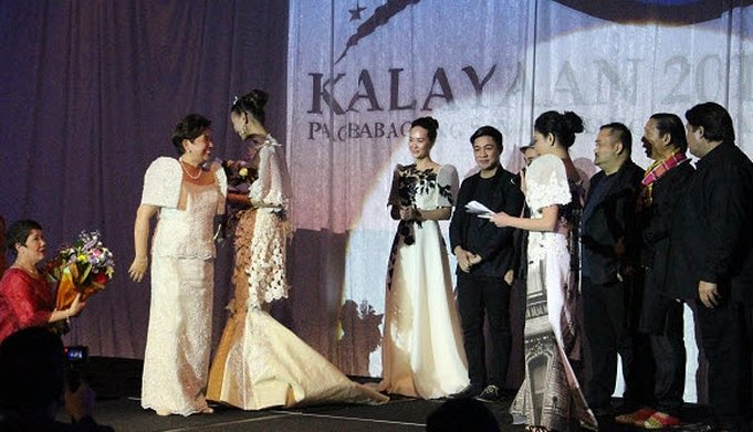 Her Excellency, Ambassador Minda Calaguian-Cruz gives flowers to one of the international models as the top designers of the Philippines look on.