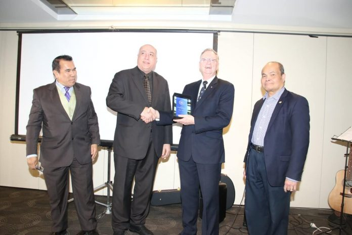 Dr Allan Terrett, a former Associate Professor of RMIT University awards plaque to ACME's Entrepreneur of the Year Sam Afra. Looking on are Fred Jover (left), ACME past president), and Walter Villagonzalo, Deputy Mayor of Wyndham and founder of Migrant Hub.