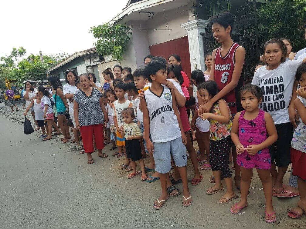 The long line in front of Midel's house during the school supplies distribution.